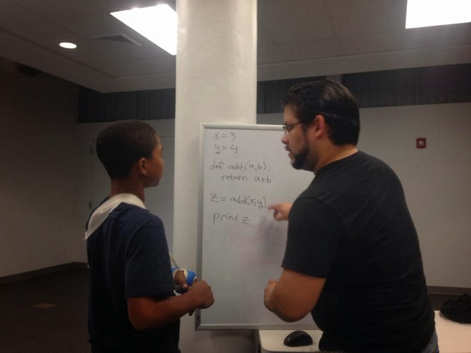 Picture of two people in front of a whiteboard in a white room. The older of the two is explaining some computer programming concepts.